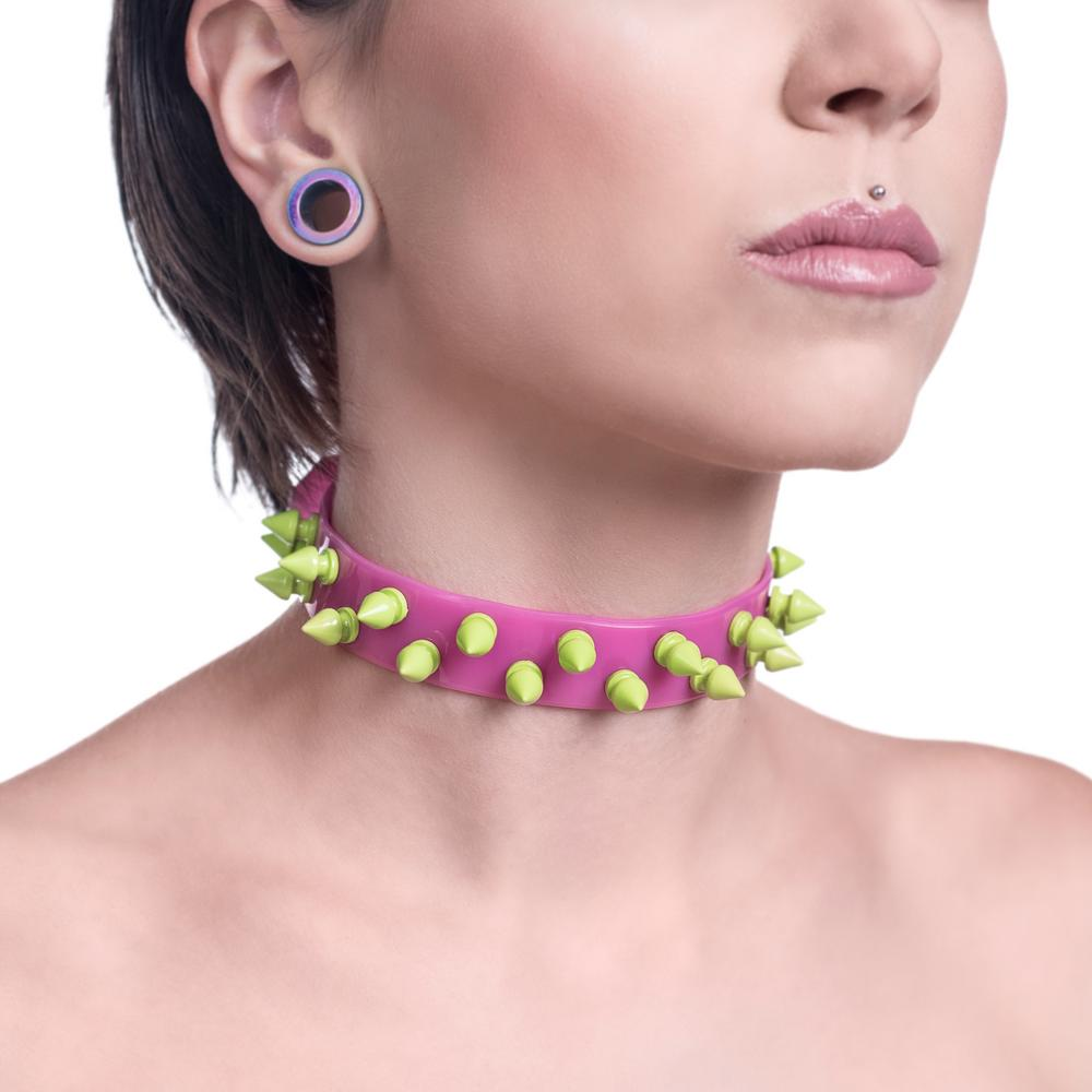 A pink choker necklace made from a 2cm stripe of PVC, with two rows of neon green metal spikes.