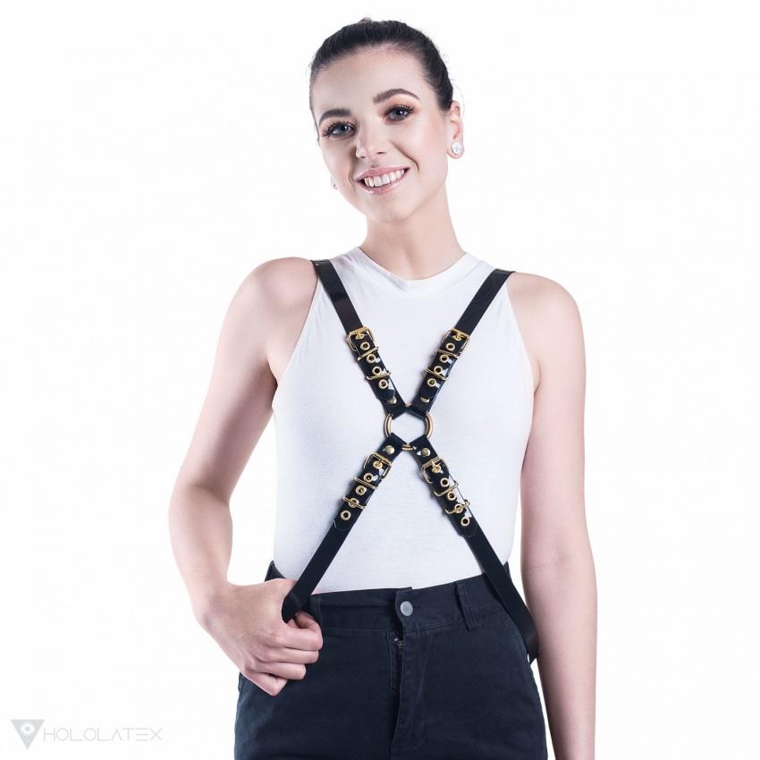 EIn schwarzer gekreuzter Harness aus PVC verbunden mit einem goldenen Metallring in.