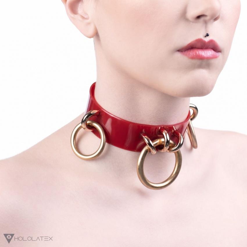 Ein Choker Halsband in semi-transparenter roter Farbe verziert mit Ringanhängern.
