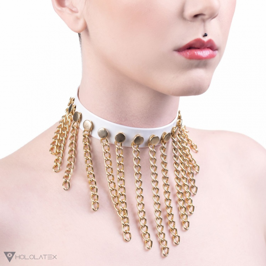 Ein weißes Choker Halsband verziert mit goldenen Ketten.