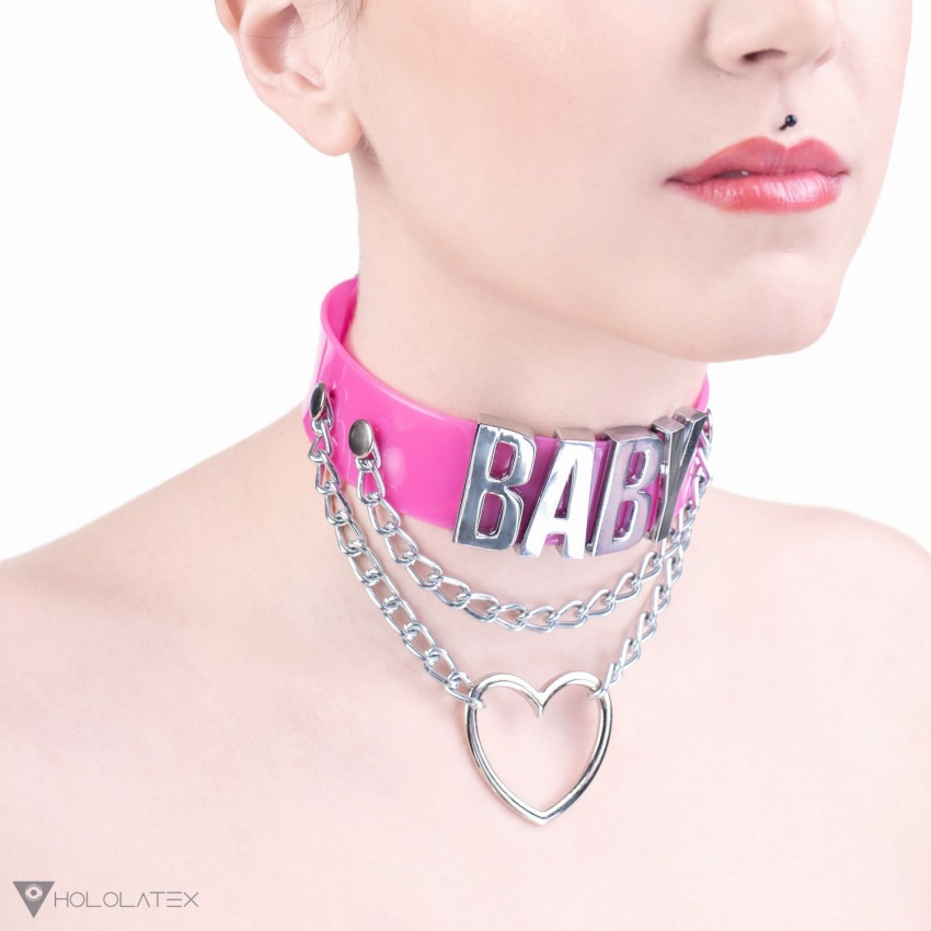 A pink choker necklace with a big sign spelling out BABY, hanging chains and a metal heart.