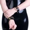 Ein Armband verziert mit einem Ringanhänger in goldener Farbe.