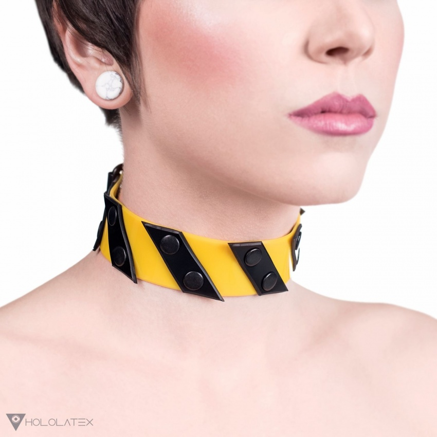 The yellow-black choker - collar creates the impression of a warning tape.