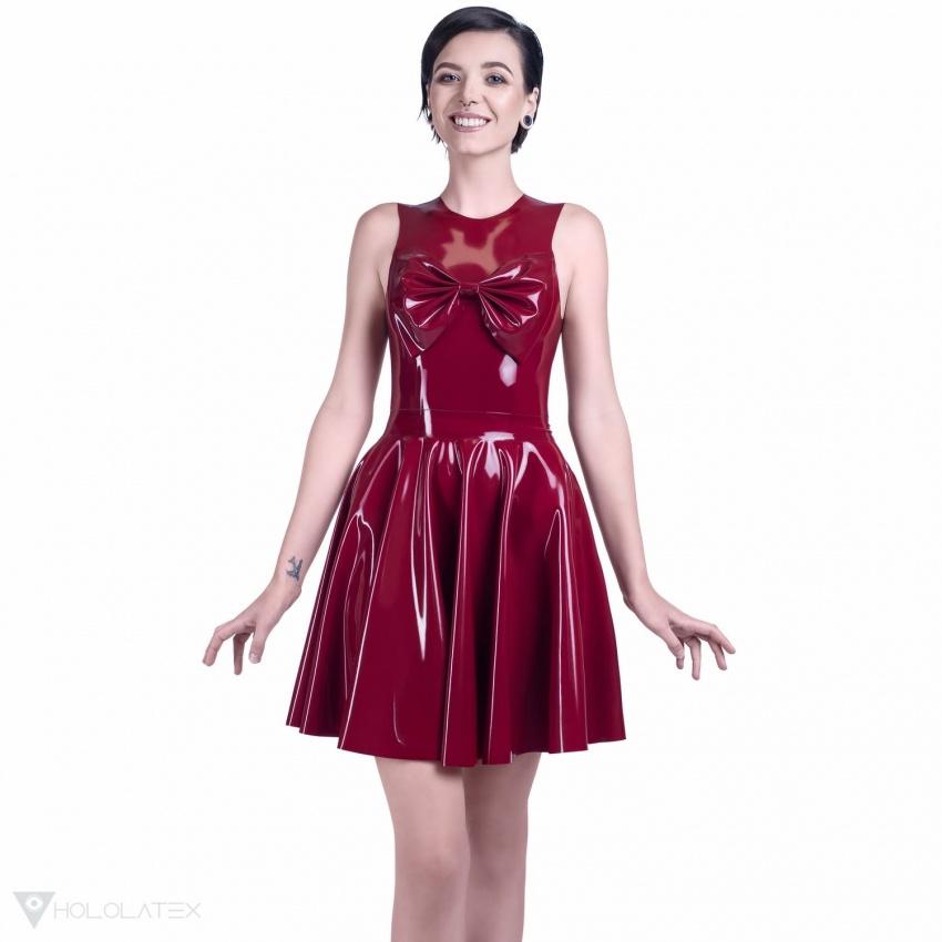 Latexové šaty ve vínové barvě s kolovou sukní po kolena, zdobené vpředu velkou mašlí stejné barvy.