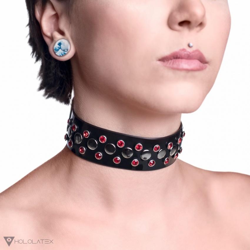 Široký choker z černého PVC, zdobený červenými kamínky, a nýty ve stříbrné barvě.