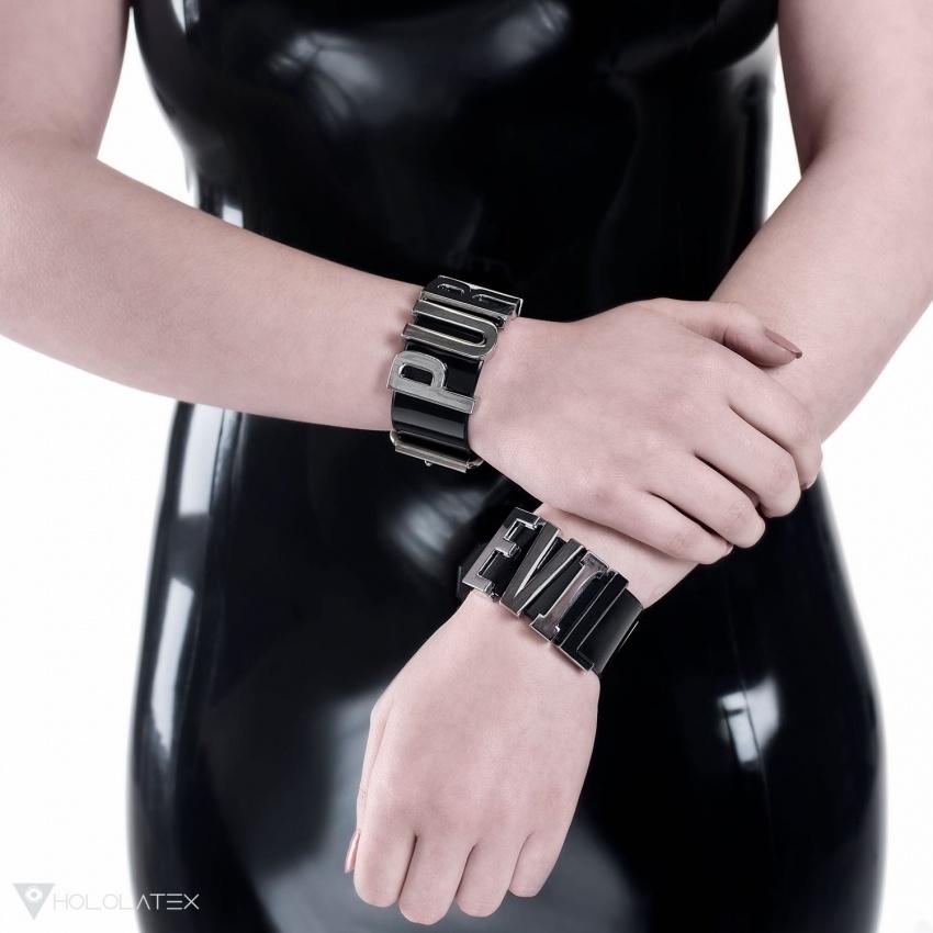 Schwarze Armbänder aus PVC verziert mit den Aufschriften PURE und EVIL aus Metallbuchstaben.