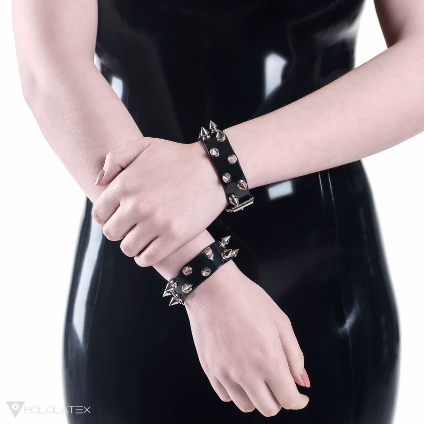 A black PVC bracelet decorated with two rows of small metal spikes in silver colour.