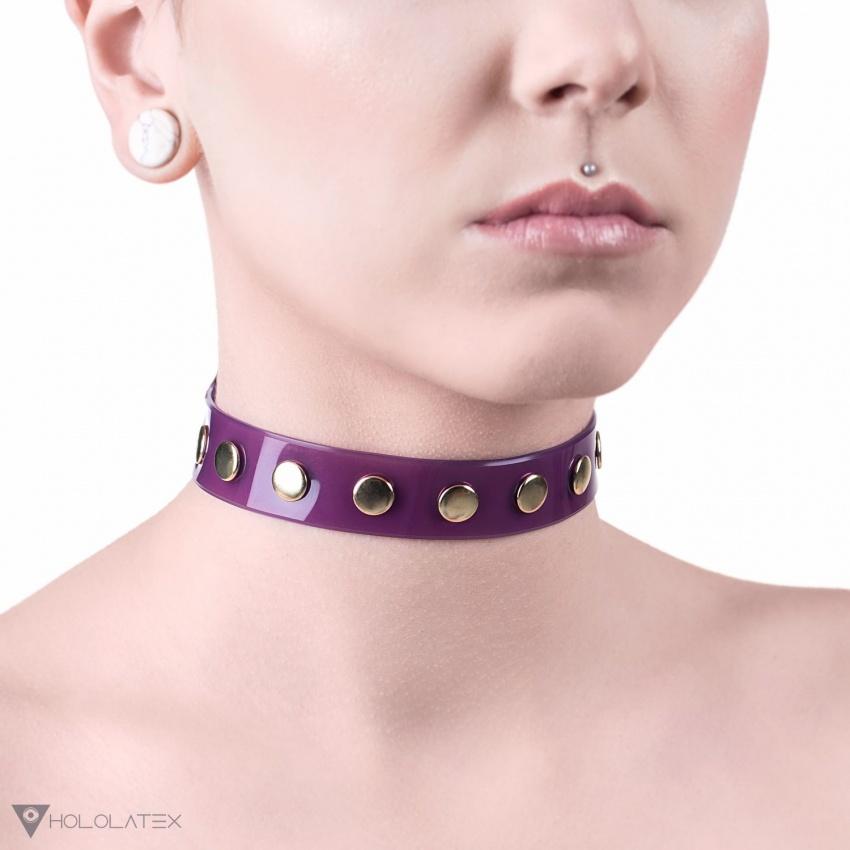 Jednoduchý choker na krk z poloprůhledného fialového PVC ozdobený řadou nýtů ve zlaté barvě.