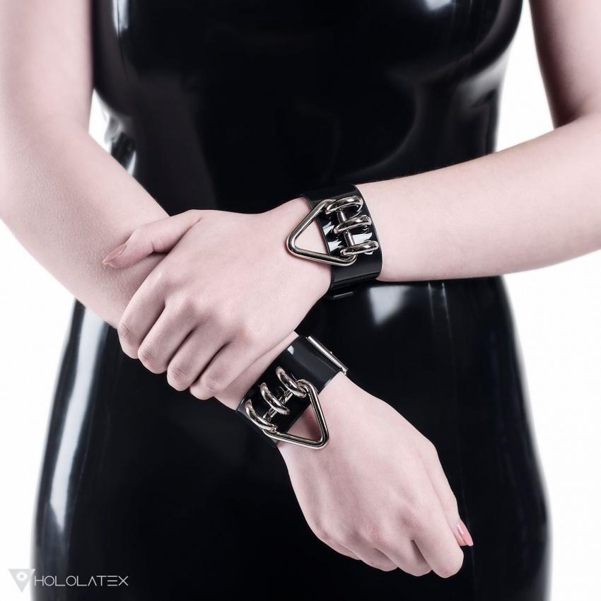 Černé náramky z PVC, zdobené zavěšenými kovovými trojúhelníčky.