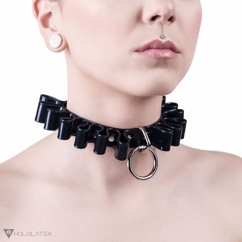 A choker necklace from black PVC with ruffles alongside its entire length. Decorated at the front with a hanging ring.