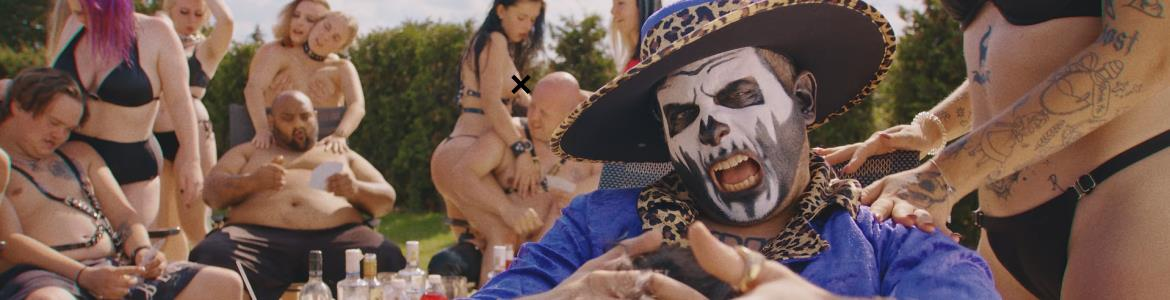 Blog header - Rapper Řezník in his new music video surronded by girls.